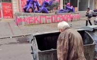 Възрастен мъж рови в контейнер за боклук на фона на боядисания паметник пред централата на БСП
